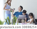 Parents are talking together while their children are studying. 30698254