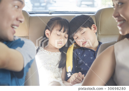 The siblings are napping in the car behind their parents. 30698280