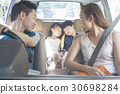 Two children are napping in the car while traveling with parents. 30698284