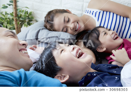 a family of parents and two children is lying and smiling 30698303