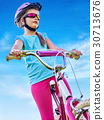 Child traveling bicycle in rainbow goggles and 30713676