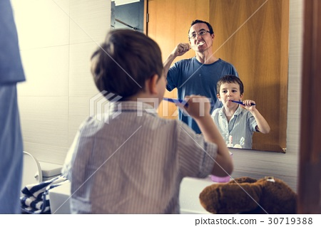 Father teaching the son how to brush his teeth 30719388