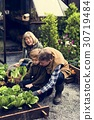 Group of people gardening backyard together 30719484