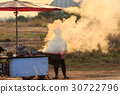 Man grilling chicken on charcoal stove with a lot smoke at food market in Thailand 30722796