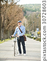 Senior man in blue checked shirt with bicycle in 30728603