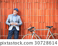 Senior man with bicycle standing against brick 30728614