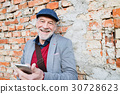 Senior man with smartphone against brick wall 30728623