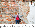 Senior man with smartphone against brick wall. 30728624