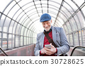 Senior man with smartphone against glass ceiling 30728625