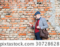 Senior man with smartphone against brick wall 30728628
