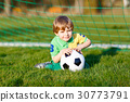 Little cute kid boy of 4 playing soccer with 30773791