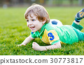 Little cute kid boy of 4 playing soccer with 30773817