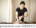 The therapist is massaging the leg of a woman in spa. 30800433