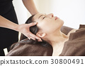 a woman gets a head massage in spa 30800491