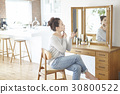 woman sits in front of a mirror and powders when making up at home. 30800522