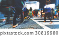 Motion blurred people walking in the city at night 30819980