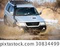 Mitsubishi Pajero Sport on dirt road in early spring making spla 30834499