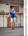 Fit athletic young man using a skipping rope 30857990