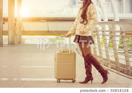 Businesswoman traveler with luggage at city 30858108
