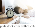 Sleeping asia woman and alarm clock is waking up 30873516