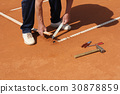 Worker Repairing lines on a tennis court 30878859