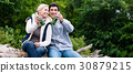 Lovers in vacation sitting at waterside clinking 30879215
