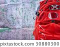 Big tourist orange backpack against map background 30880300
