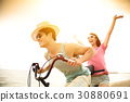 happy young couple riding bicycle on the beach 30880691