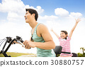 father with daughter riding bicycle  outdoors 30880757