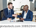 Black businessman shaking hands with a caucasian one in office 30892044