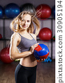 Young fitness girl standing with medicine ball 30905194