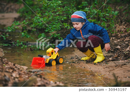 little boy playing with toy truck 30943197
