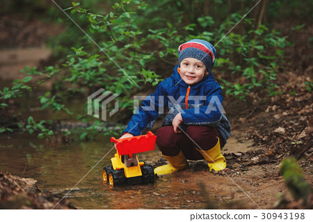little boy playing with toy truck 30943198