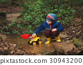 little boy playing with toy truck 30943200