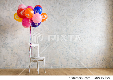 Chair and balloons on the wooden floor in the room 30945159