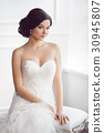 Bride in beautiful dress sitting on chair indoors 30945807