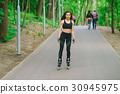 Sports girl in the park on roller skates 30945975