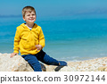 Smiling child sitting on a rock with seascape on 30972144