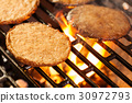 Hamburger patties on a grill with fire under 30972793