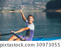 A Young single scull rowing competitor paddles on 30973055