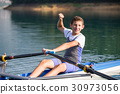 A Young single scull rowing competitor paddles on 30973056