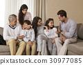 Happy multi-generation family sitting on sofa 30977085