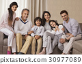Portrait of smiling multi-generation family sitting on sofa 30977089