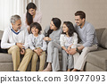Happy multi-generation family sitting together on sofa 30977093
