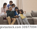 Happy Family looking at digital tablet while sitting together on sofa 30977094