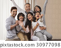 Cheerful multi-generation family sitting together 30977098