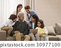 Happy multi generation family looking at digital tablet 30977100