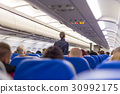 Stewardess walking the aisle of commercial 30992175