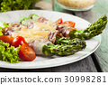 Baked green asparagus with prosciutto and cheese 30998281