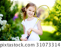 Cute little girl playing badminton outdoors 31073314